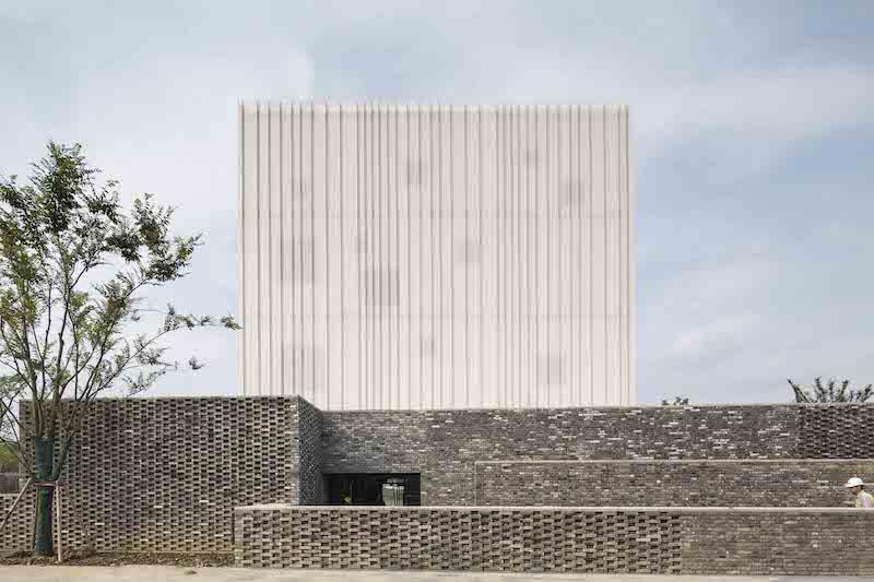 La cappella, con il suo rivestimento bianco traforato, si eleva verso il cielo e poggia su basamento in mattoni grigi © Pedro Pegenaute
