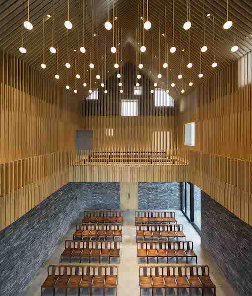 Vista interna della cappella, avvolta da un rivestimento ligneo che forma la sagoma di una capanna e dona all'ambiente un'atmosfera calda e spirituale © Pedro Pegenaute