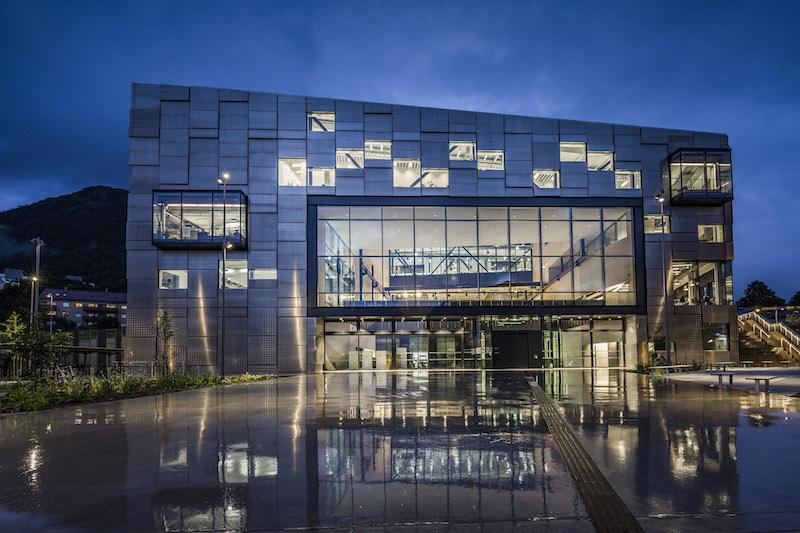 Visibile anche dall'esterno, la grande Project Hall al piano primo è il cuore dell'edificio - vista notturna del prospetto d'ingresso © Tomasz Majewski Photography