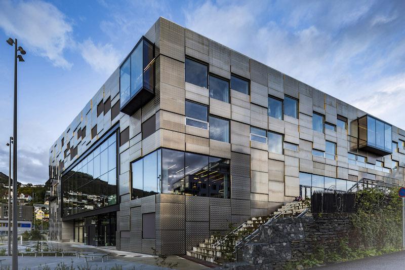 L'involucro esterno dell'edificio presenta un puzzle di pannelli grezzi in alluminio alternato a finestre casuali, superfici vetrate e box a sbalzo © Tomasz Majewski Photography