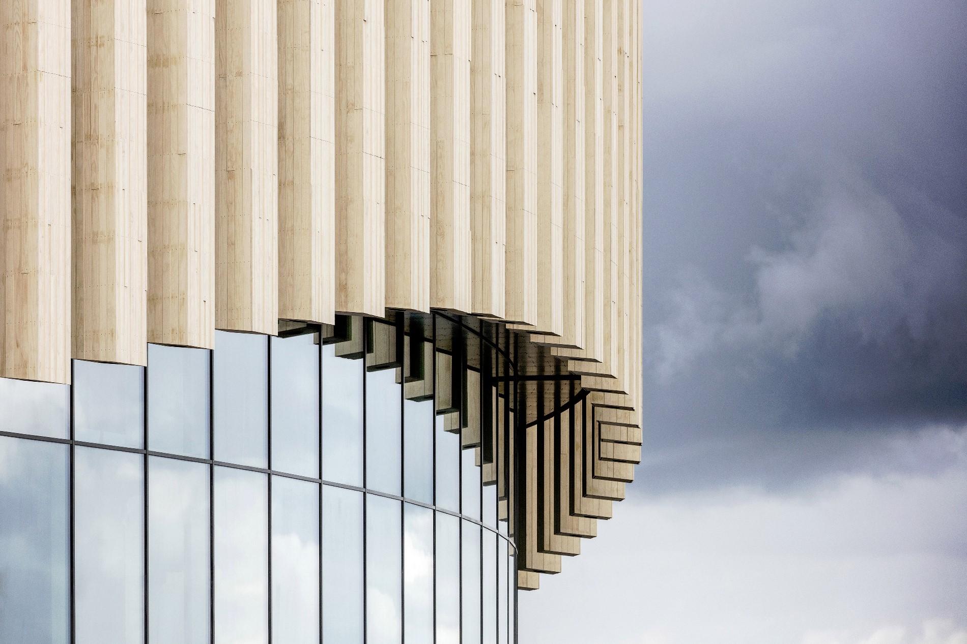 La facciata ondulata semitrasparente sembra danzare sopra il podio circostante sollevandosi leggermente in corrispondenza degli ingressi © Adam Mørk