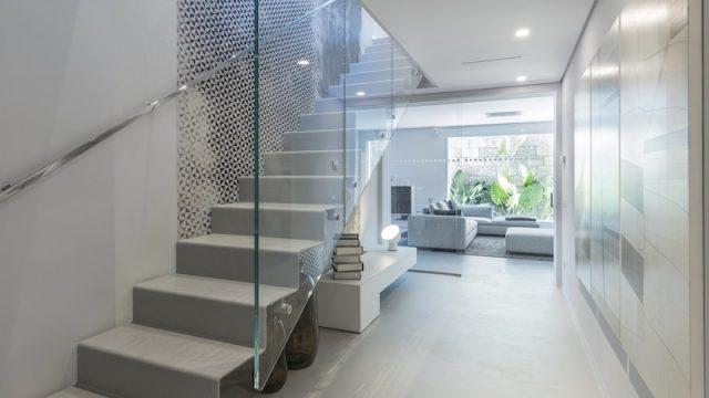 Stile minimal ed elegante all'interno: la scala in vetro e acciaio.
