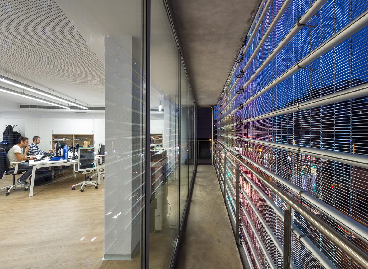Gli uffici si relazionano con l'esterno grazie a superfici vetrate schermate da un involucro in rete metallica © Simón García/arqfoto