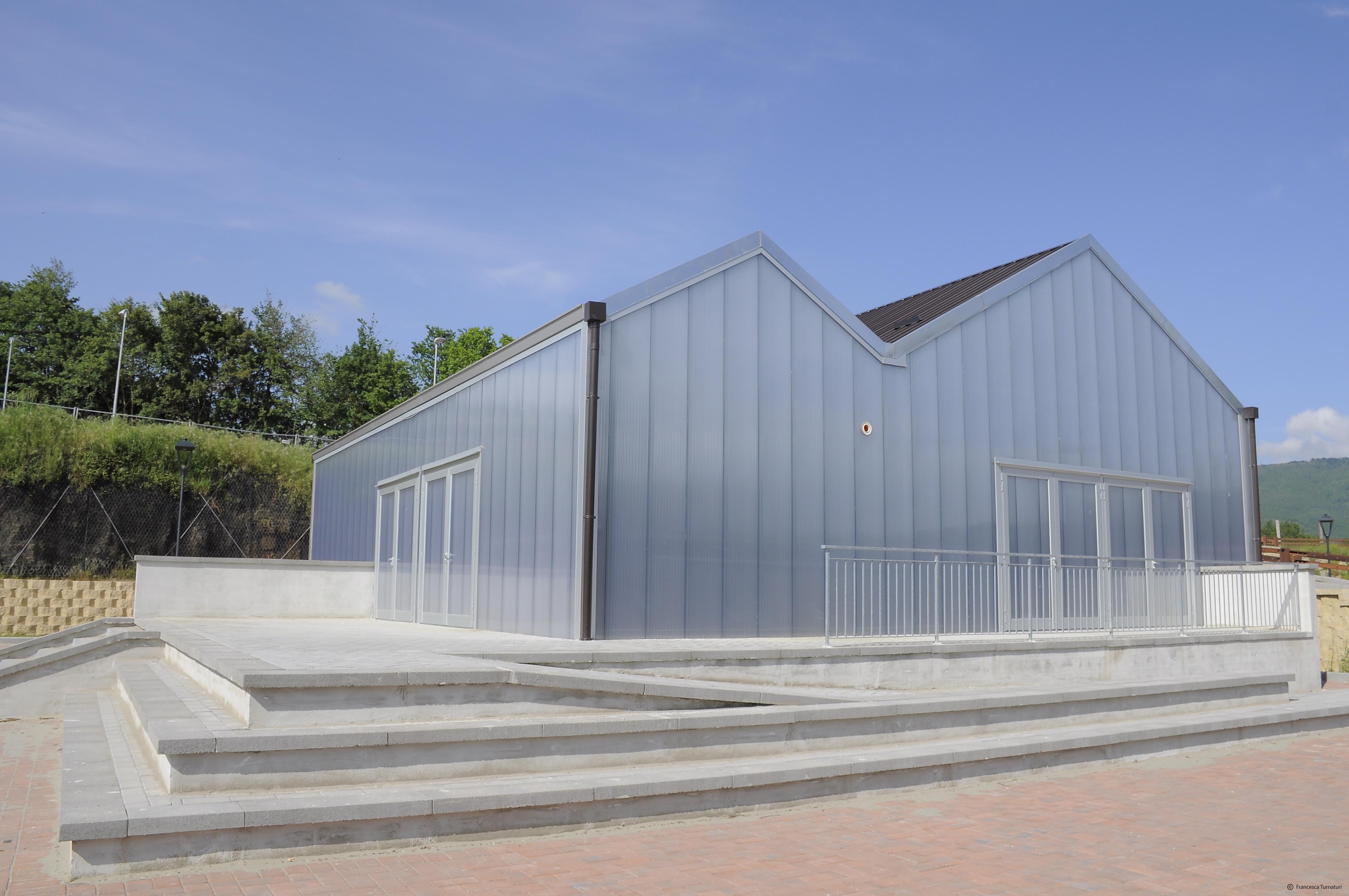 Esternamente l'edificio si presenta come un volume compatto, avvolto da un rivestimento in policarbonato semitrasparente © Francesca Turnaturi